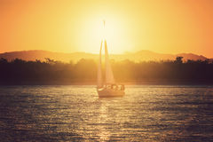 Sailing yacht against sunset Stock Photography