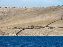 Sailing on a yacht along an island village in Croatia, farming alone on an empty desert island, Kornati national park. Summer Stock Image