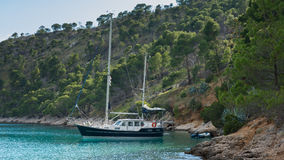 Sailing yacht anchored before rocky beach before monestary 'Blaca' in Croatia. In Croatia there is a monestary named 'Blaca'. This place can be reached by a Royalty Free Stock Images
