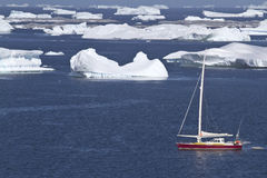 Sailing yacht in Antarctic waters between icebergs Stock Photo