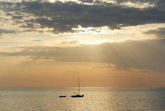 Sailing yacht with attached rubber boat at sunset. The sailboat is in the sea, a rubber boat, a sunset, the sun`s rays are piercing through the clouds Stock Photos