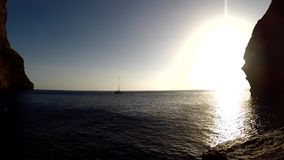 Sailing yacht in the bay among the rocks. Cove at the foot of the cliffs of Los Gigantes, Canary, Tenerife stock video footage
