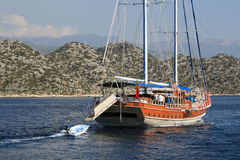 Sailing yacht with a boat behind in the Aegean Sea Stock Photos