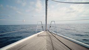 Sailing on yacht boat. Front view on luxury sailing yacht boat nose with wooden parquet floor, swaying in open sea at sunny day. Relaxing and peaceful background stock video