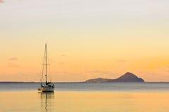 Sailing yacht on calm sea at sunset Stock Photos