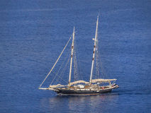 Sailing yacht. Cruising with lowered sails on calm sea Royalty Free Stock Photography