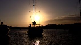 Sailing yacht against the backdrop of the setting sun. Sailing yacht enters the marina against the backdrop of the setting sun stock video