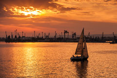 Sailing yacht enters Varna harbor at the sunset Royalty Free Stock Photos