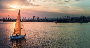 Sailing yacht enters Varna harbor at the sunset Stock Images