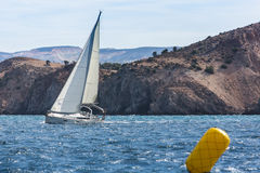 Sailing yacht in the finish during the race regattas near the coastal cliffs Stock Images