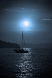 Catamaran sailing in the sea during a full moon Royalty Free Stock Image