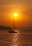Catamaran sailing in the sea at sunset Stock Images