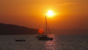 Sailing yacht illuminated by the light of the sun setting. Stock Image