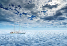 Sailing yacht on a peaceful ocean voyage. A small sailing yacht on a dreamy ocean with misty waves royalty free stock images