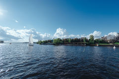 Sailing yacht sails past the dock at private homes Stock Photography