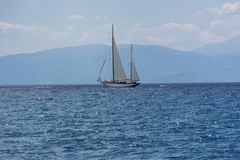 Sailing yacht in the sea, in the distance you can see the coast. With mountains, view of the Corinthian Gulf and the island of Peloponnese, Greece, boat in the Royalty Free Stock Photography