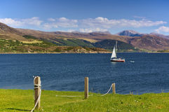 Sailing yacht at sea with mountain range in the background Royalty Free Stock Images