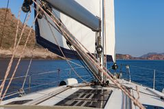 Sailing yacht on the sea. Sailing boat with white deck and white sails, sail away, in Greece, Cyclades islands, freedom and move Royalty Free Stock Photo