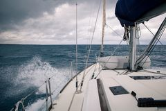 Sailing yacht during a storm, the view from the bow of the ship. The large waves and cloudy sky royalty free stock images