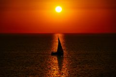 Sailing yacht in the sunset, the shadow of the sailboat on the background of the Golden sunset and reflection in the royalty free stock photo
