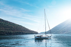 Sailing yacht swimming at blue sea near mountains. Sailing yacht swimming at blue sea near forest mountains Royalty Free Stock Photography