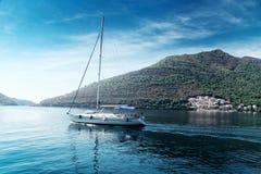 Sailing yacht swimming at blue sea near mountains. Sailing yacht swimming at blue sea near forest mountains Royalty Free Stock Photos