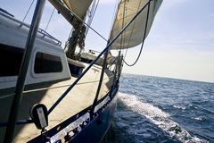 Sailing yacht under the sails. In the sun with blue sea Royalty Free Stock Image