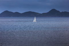 Sailing yacht with white sails in the open sea Stock Photo
