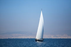 Sailing yacht with white sails in the sea near coast. Luxeru. Royalty Free Stock Photo