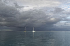 Sailing yachts and cloudy sky. Two sailing yacht at the mooring under cloudy weather Stock Image