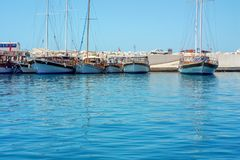 Sailing yachts on the pier on the background of stones stock image