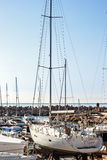 Sailing yachts and pleasure boats stand moored in port. Against a blue sky Royalty Free Stock Image