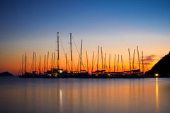 Sailing yachts silhouettes. Over a beautiful sunrise in a Greek island Stock Photos