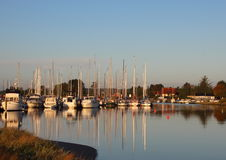 Sailing Yachts in Small Harbor with Reflections in Water Royalty Free Stock Photography
