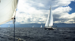 Sailing  yachts with white sails in stormy weather. Royalty Free Stock Photos