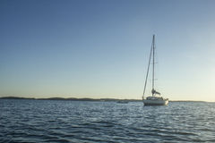 Sailingboat anchored on calm sea near islands Royalty Free Stock Photos