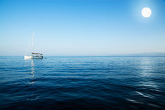 Sailingboat with the moon. On calm water Stock Photography