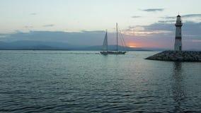Sailling fartyg som kommer till marina med konturn av fyren och soluppgång på bakgrunden 4K stock video