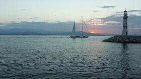 Saillingsboot die aan de jachthaven met silhouet van vuurtoren en zonsopgang op de achtergrond komen 4K stock video