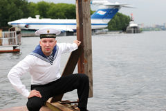 Sailor. A young sailor in the form of sitting on the dock at the river royalty free stock photography