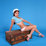 Sailor. Girl sitting on an old wodden trunk. Done in a modern pin-up style Royalty Free Stock Photography