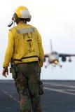 Sailor and Aircraft. A sailor watches as a naval aircraft lands aboard an aircraft carrier Stock Images