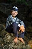Sailor boy sitting on a stone stock photo