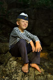 Sailor boy sitting on a stone stock images