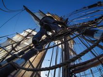 Sailor climbing rigging of traditional tallship or sailboat Stock Image