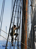Sailor climbing ship rigging. Sailor climbing rigging of old masted ship with sea in background Stock Photo