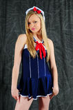 Sailor Clothes. Young female fashion model standing against a charcoal back ground wearing a sailor outfit looking at the camera with a matching hat on her head royalty free stock photography