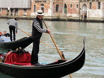 Sailor driving tourists in a gondola in Venice Stock Images
