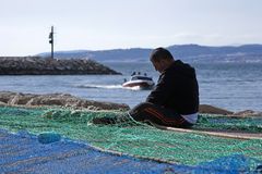Sailor fixed their fishing nets in the port of Estepona Stock Image