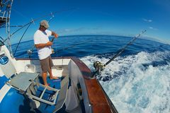 Sailor gets ready reels and rods for marlin game fishing at sea near Saint-Denis, Reunion island. stock photography